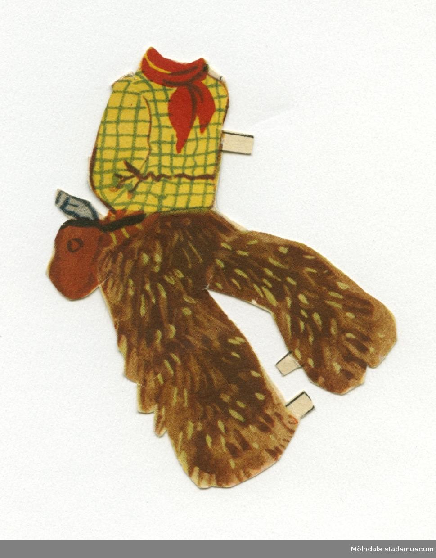 """Klädesplagg till pappersdocka, urklippt ur tidning på 1950-talet. Dockan saknas dock.Urklippet föreställer en cowboydräkt; skjorta, pälsbyxor, samt revolver i hölster. Det förvaras i ett vitt C6-kuvert, märkt """"Indianerna"""", men ursprungligen poststämplat i Åbo, Finland 1953, till familjen. I kuvertet förvaras också ytterligare en pappersdocka (MM 04650)."""