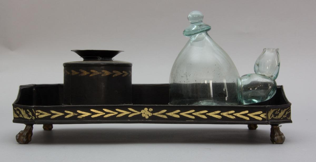 Skrivtyg tillverkat av bemålad plåt. Till skrivtyget finns sandströare i plåt och bläckhorn i glas. Sandströare och bläckhorn har fästen i själva skrivtygets platta. Runt om plattan perforerad kant. Skrivtyget vilar på fyra bronserade lejontassar.