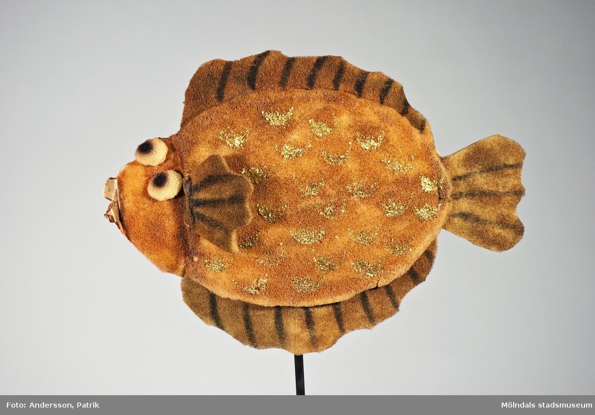 """Kasperdocka - """"Den förtrollade fisken"""" - från berättelsen med samma namn. Fisken går i brunt och rödbrunt, med """"fjäll"""" av guldglitter. En pinne som är menad att hålla i och """"styra"""" fisken med är fäst i underkantGivaren Blanka Kaplan var förskollärare och använde dock-teater i sin pedagogik. De sista åren före sin pension åkte hon runt i olika förskolor med sina föreställningar. Hon var ledare för dockteatern """"Tusensköna"""", som spelade klassiska sagor i tjeckisk tradition. Blanka Kaplan är född i Tjeckoslovakien och kom till Sverige 1968.(se bilaga i arkiv)."""