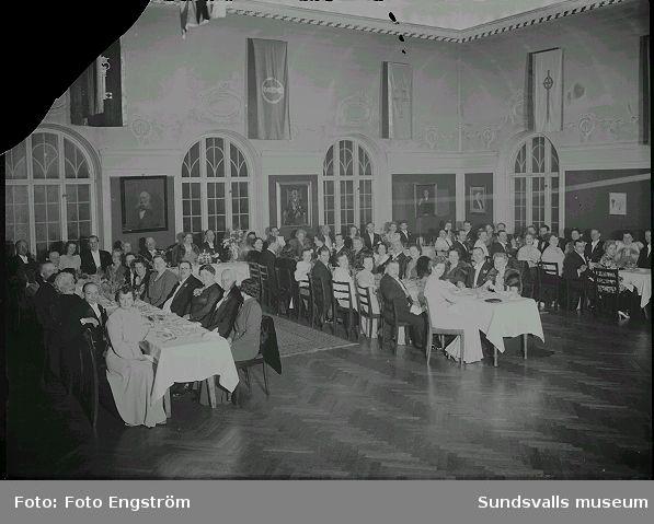 Festmiddag, män och kvinnor vid dukade bord i festlokal.