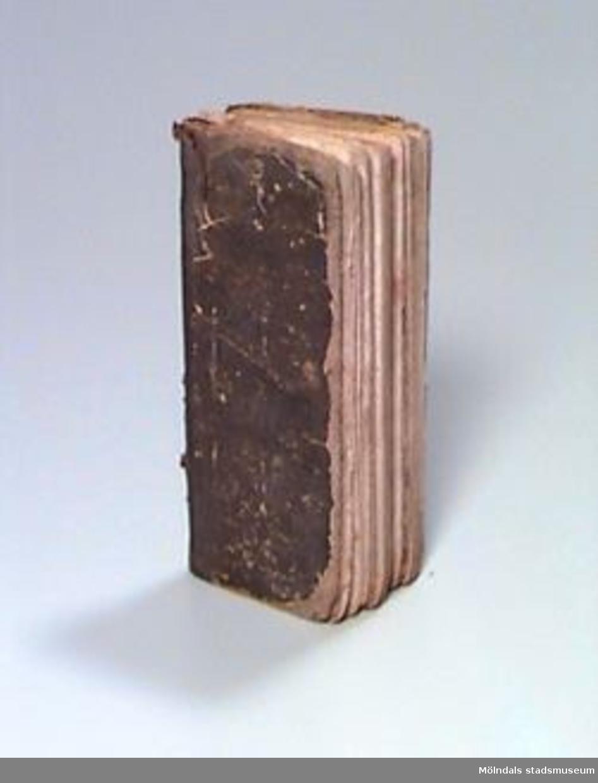 """""""Lärobok för folkskolor; innehållande de första begreppen af allmän Geografi och Historie, Swenska och Norrska Historien, Naturläran, Tidräkningen, Mythologien, Religionen, Arithmetiken, mm"""".Pärmen klädd med brunt dekorerat papper. På främre pärmens insida finns ett oläsligt namn skrivet med bläck, möjligen är förnamnet """"Carl"""". På bakre pärmens insida står med bläck: """"Den 10 maj 1844"""" samt initialer som kan vara """"C:c"""" och """"L:d"""" (där """"d"""" står för """"dotter"""") och ett efternamn som troligen är """"Maak""""."""