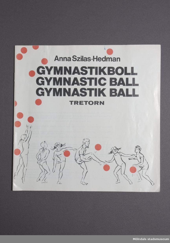 """Häftet finns även med engelsk och tysk översättning i samma utgåva. Sidorna är tunna och glansiga.Namnet är """"Gymnastikboll"""" på svenska.På omslaget ser man en massa människor som utför olika konster med bollar."""
