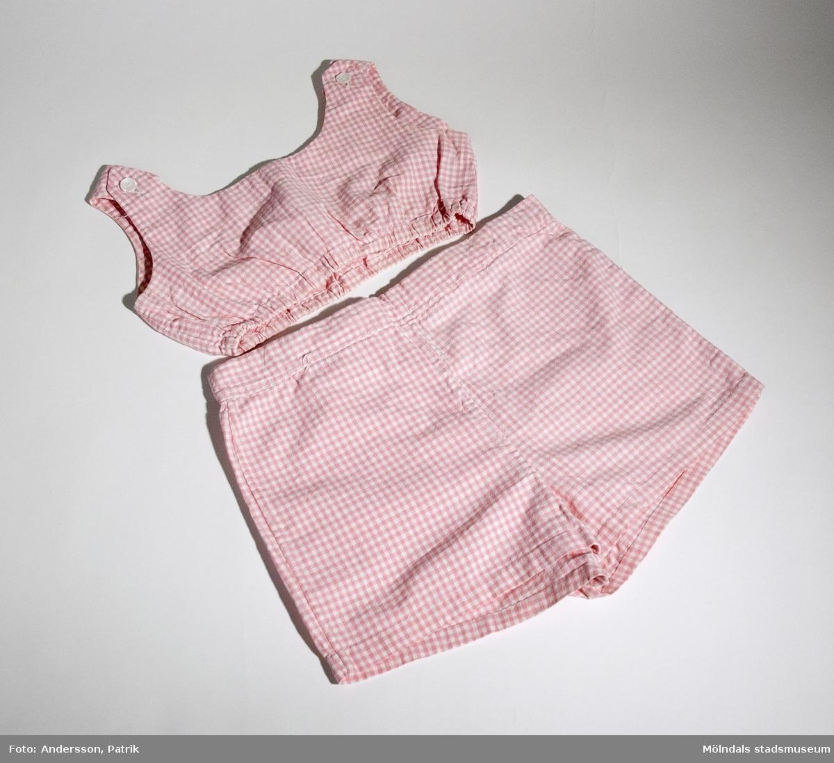 Tvådelad soldräkt för barn. Består av armlös kort överdel och kortbyxa. Rosa rutigt tyg.