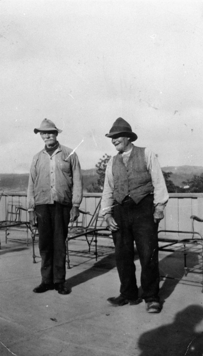 """Två män som bodde på isoleringen på Kärra Hökegård. Kortet är taget på en sorts vilaltan där """"hjonen"""" rastades. Fr.v. Josefsson, kallad """"sjömannen"""", från Krokslätt och Edvard. Kärra Hökegård var ett försörjningshem för såväl senildementa som psykiskt sjuka, utvecklingsstörda och ensamstående mödrar. Verksamheten försvann i och med att Lackarebäckshemmet stod klart 1951."""