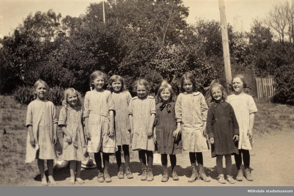 """Gruppfoto av skolklass vid Holtermanska skolan. Flickorna i klassen, fr.v. ?, ?, Margit Wallin, ?, ?, Estrid Wallman, Daga, ?, Elsa Börjesson.     Direktören Martin Holterman i Ostindiska kompaniet ägde Åby gård. 1782 skänkte han 3000 daler silvermynt till Fässbergs församling + ett nybyggt skolhus och trädgård på gårdens ägor vid Åby by. I skolan skulle 10 fattiga barn undervisas i """"kristendom, skrivande och något räknande. Holtermans skola fanns kvar till 1875. Då hade donationens ändamål ändrats, och man byggde i stället ett barnhem kombinerat med småskola. 1914 brann barnhemmet och 1915 byggdes ett nytt barnhem på samma tomt. 1929 överlämnades barnhemmet till Mölndals stad."""