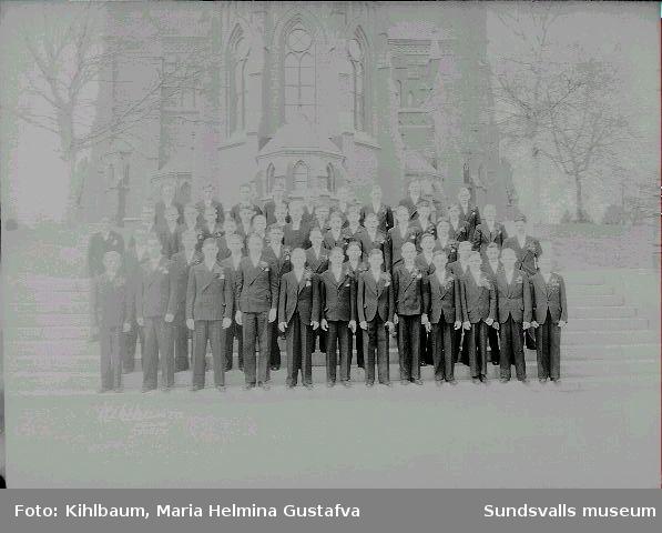 Grupporträtt framför Gustav Adolfs kyrka. Konfirmation, pojkar.