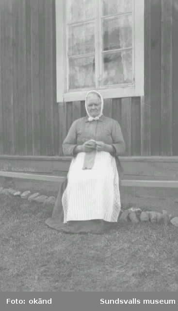 Porträttt av äldre kvinna sittandes utanför bostaden