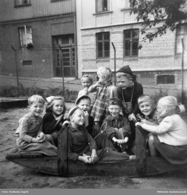 Barn som sitter ute på en lekplats. 1940-tal, plats okänd.