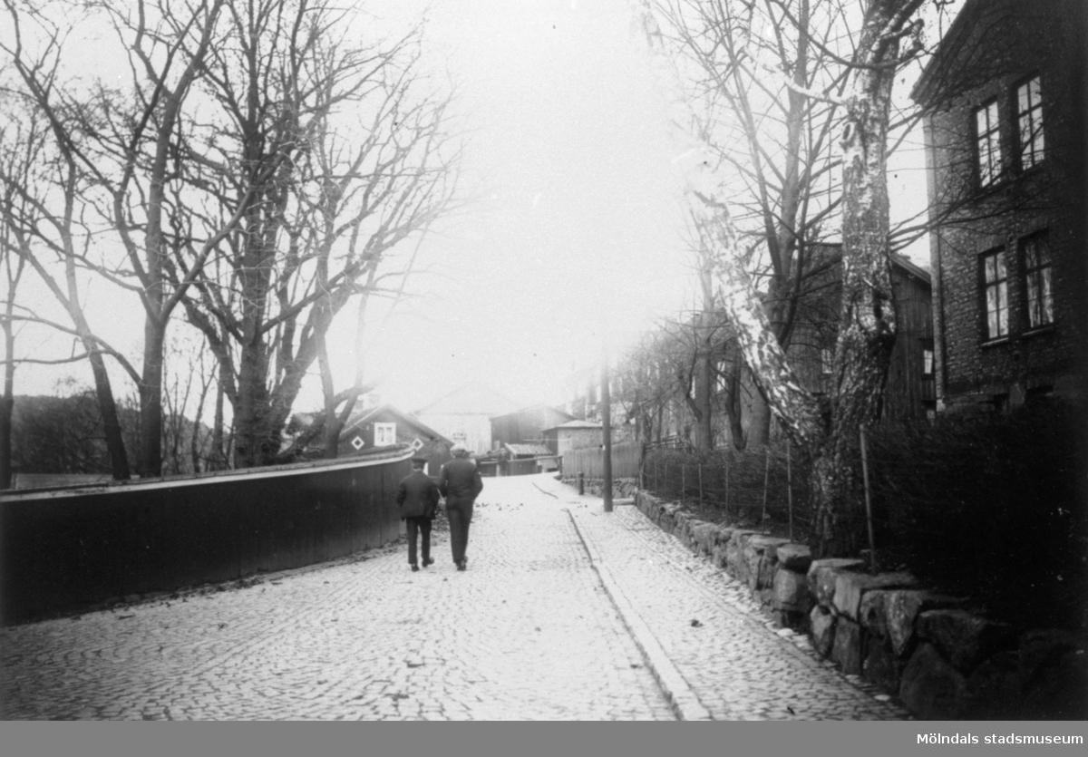 Två män promenerar på Forsåkersgatan mot norr. Till höger syns sjukstugan (senare polishus och Mölndals museum) samt Svennings hus. Norra Forsåkersgatan 19, år 1921.