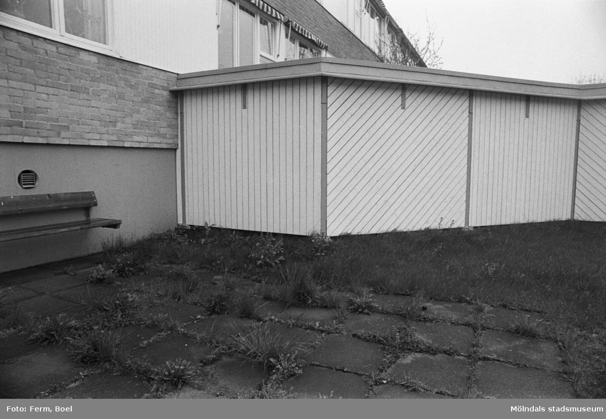 Dokumentation av Sagåsens flyktingförläggning 1992. Exteriör vy mot insynsskydd, bänk, gräsmatta och byggnad.