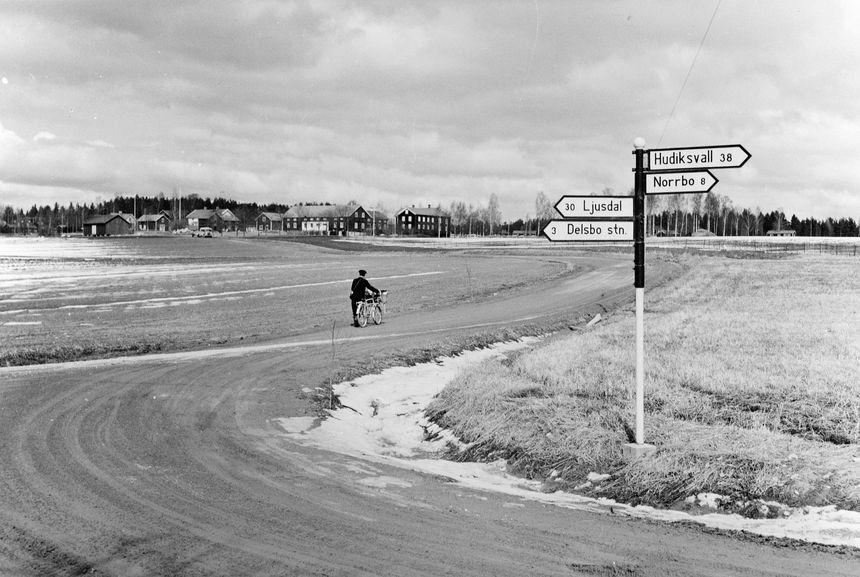 Lantbrevbärare, postiljon Erik Bergman (cykelåkande) i Delsbo.  April 1956. Brevbäringsturen är 2 ½ mil lång och omfattar nästan 300 hushåll.  Postväskan väger ofta 30-40 kg.