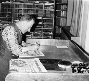 Lantbrevbärare Ruben Carlsson skriver på dagstidningar före brevbäringsturen.