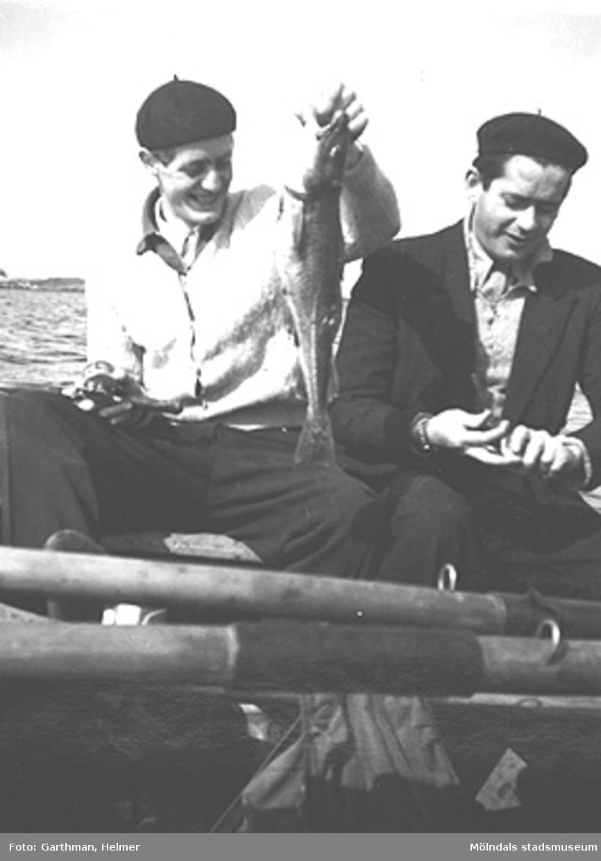 Helmer Garthmans kompis Angel Lopez (till höger) på Näset. Dagens fångst, en torsk på ca ett kilo, hålls upp av en okänd kompis. 1950-tal.