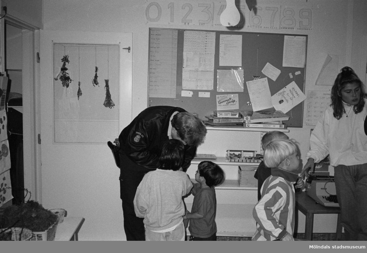 Katrinebergs daghem har besök inomhus utav polismän. Två pojkar står och pratar med en polis som lutar sig fram mot dem. Två barn stårt vänt åt andra hållet och samtalar med förskolläraren. På väggen bakom hänger en anslagstavla.