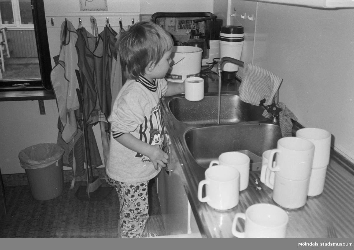 Flickan Alexandra står vid diskbänken. Hon häller upp vatten i en vit kaffemugg, ifrån en rinnande kran. Lunkentussen, Katrinebergs daghem, 1992.