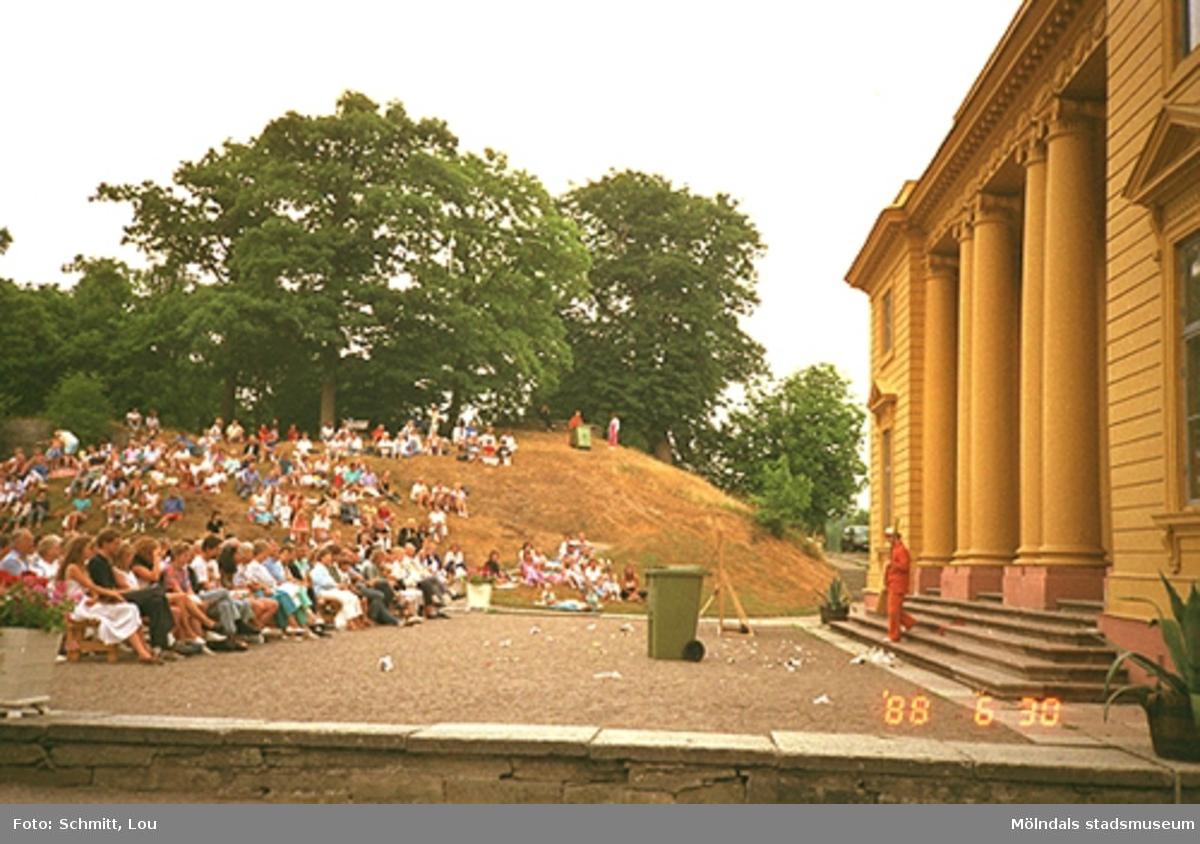 Människor som tittar på en orangeklädd person i en teaterföreställning framför Gunnebo slottsentré. Till höger ser man en del av det gula slottet.