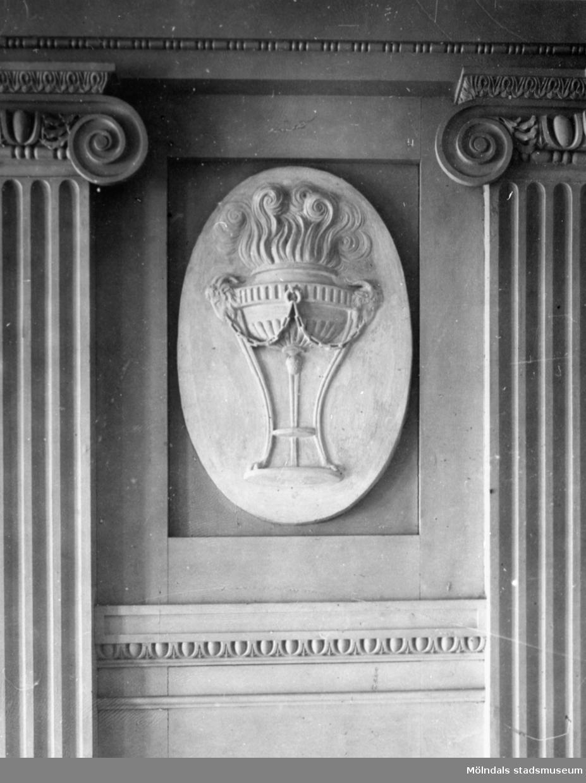 """I en tablett, en stående oval relief med emblemet """"flammor ur en trefot"""", placerad ovanför årstids-gipsfiguren """"Vintern"""" av Gioacchino Frulli (1766-1801). Denna sitter på nordvästra väggen i stora salongen på Gunnebo slott."""