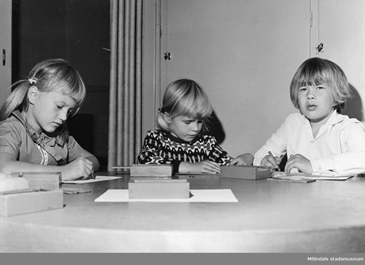Tre barn som ritar vid ett bord. Holtermanska daghemmet 1953.