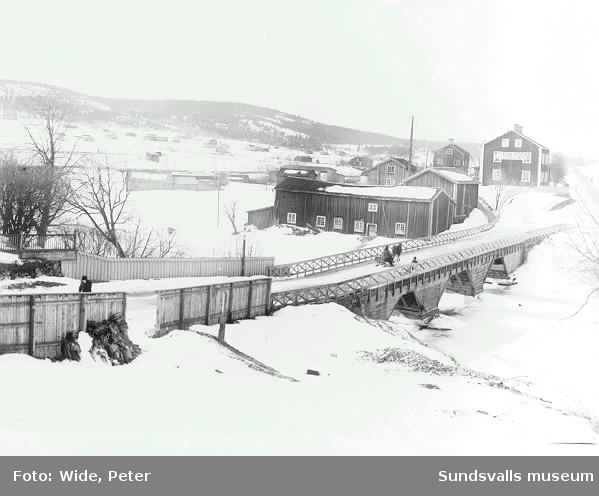 Widesbron över Selångersån. Vinter. Hästdragen släde. Peter Wides färgeri samt boningshus väster om bron. Nacksta i bakgrunden t v.