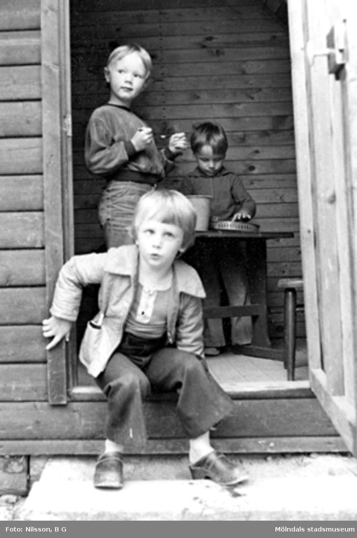 Tre pojkar som leker i en träbyggnad utanför Holtermanska daghemmet 1973.