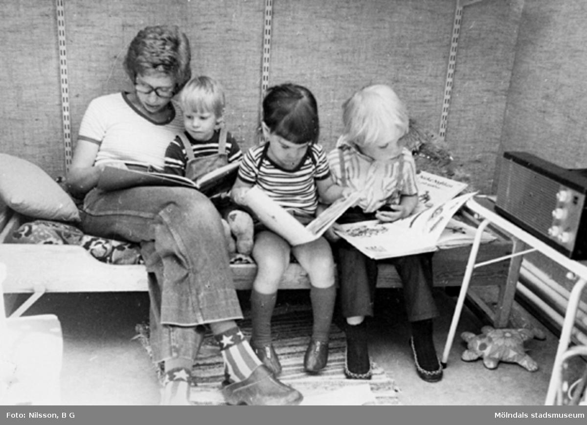 En fröken som läser för ett barn och två andra som tittar i böcker. Holtermanska daghemmet, okänt årtal.