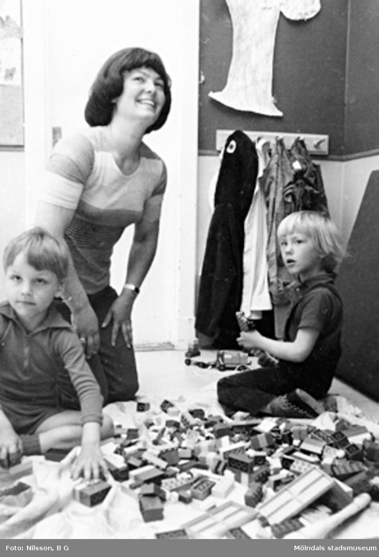 Två pojkar och en fröken som sitter på golvet och leker. Holtermanska daghemmet, okänt årtal.