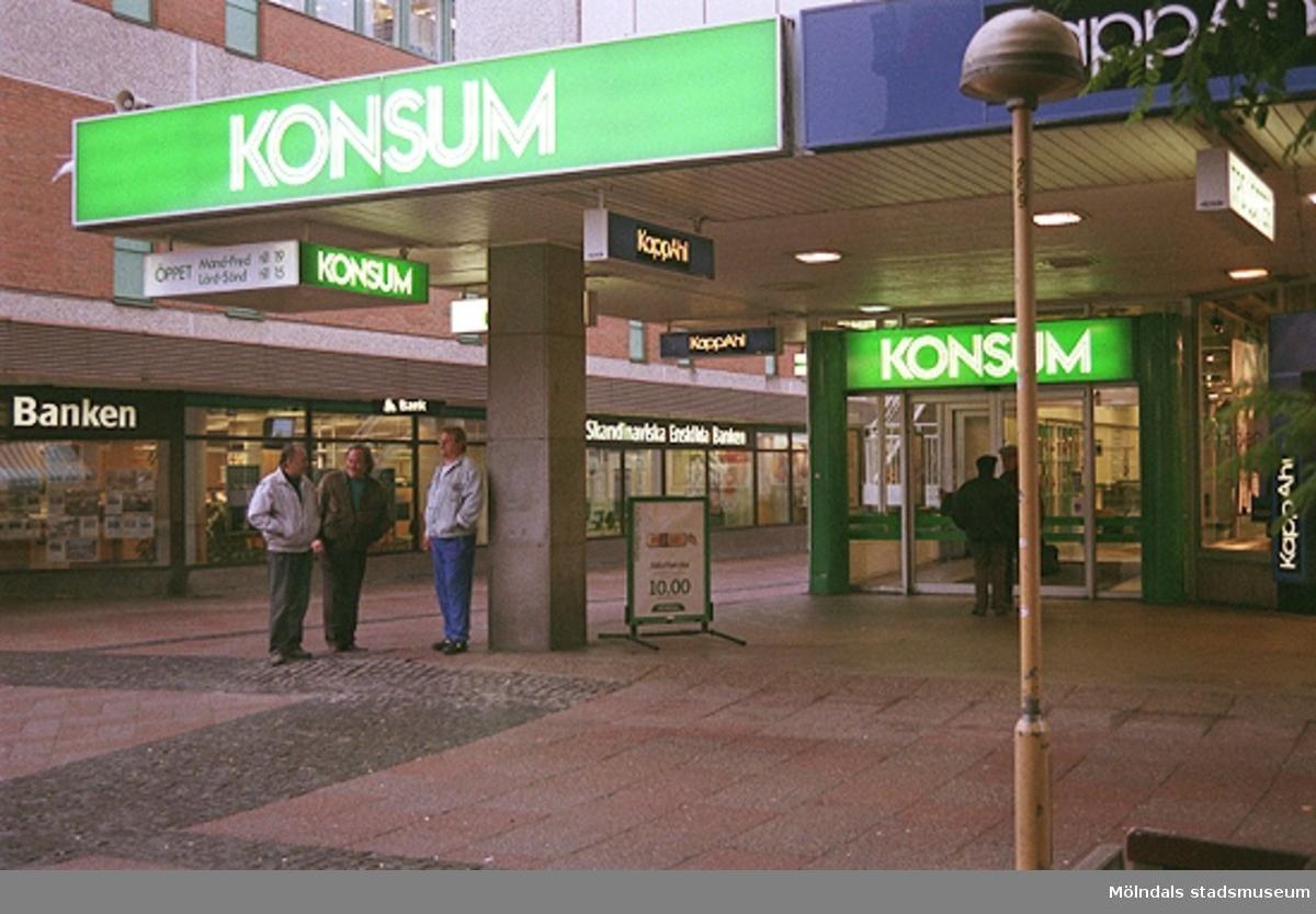 Konsum i hörnet av Brogatan och Nygatan. Mölndalsbro i dag - ett skolpedagogiskt dokumentationsprojekt på Mölndals museum under oktober 1996. 1996_1173-1187 är gjorda av högstadieelever från Kvarnbyskolan 9D, grupp 3. Se även 1996_0913-0940.