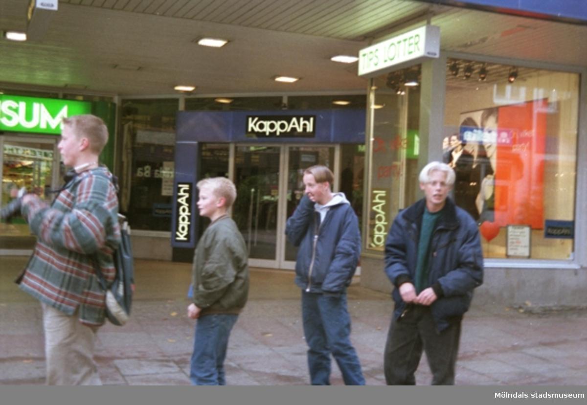 Fyra ungdomar står utanför KappAhl. Mölndalsbro i dag - ett skolpedagogiskt dokumentationsprojekt på Mölndals museum under oktober 1996. 1996_1283-1300 är gjorda av högstadieelever från Åbyskolan 8A, grupp 3. Se även 1996_0913-0940, gruppbilder på klasserna 1996_1382-1405 och bilder från den färdiga utställningen 1996_1358-1381.