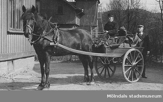 """Häst och vagn ståendes utanför ett hus. Kusken är en ung man med piska i handen. Bakom ekipaget står en äldre man. Båda har huvudbonad. Foto med undertexten """"Minne af den 22/1-1905, Wiktor."""""""