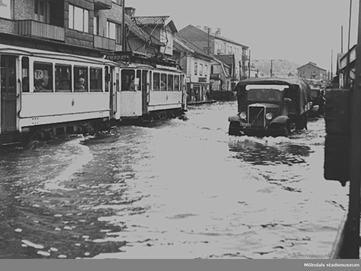 Spårvagn och bilar som forcerar fram genom översvämning på Göteborgsvägen mot norr. Man ser Göteborgsvägen 1, 3, 5, 7 och 9 på vägens vänstra sida.