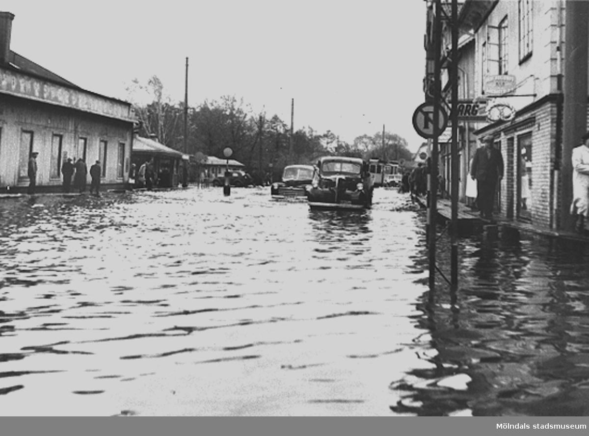 Göteborgsvägen är översvämmad och har fotograferats åt söder. Till vänster ses Fabriksförsäljningen och Pressbyråns kiosk. Till höger skymtar Göteborgsvägen 1, 3 och 5.