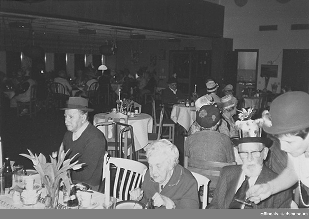 Personer iklädda fina hattar sittandes vid långbord. Okänt årtal.