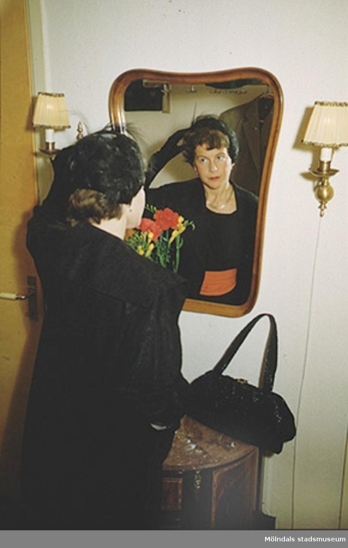 Margit rättar till sin hatt, år 1955. Hatten finns i Mölndals stadsmuseums samlingar med invnr. 03333.