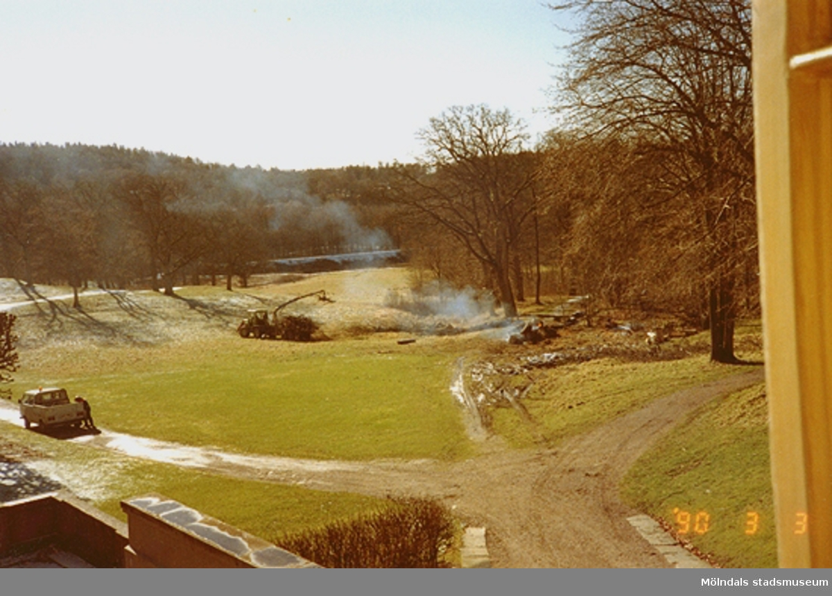 Landskapsvy från Gunnebo slott. Till vänster står en flakbil på grusvägen. Till höger ses en eld där ihopsamlat ris bränns upp. En traktor samlar ihop riset.