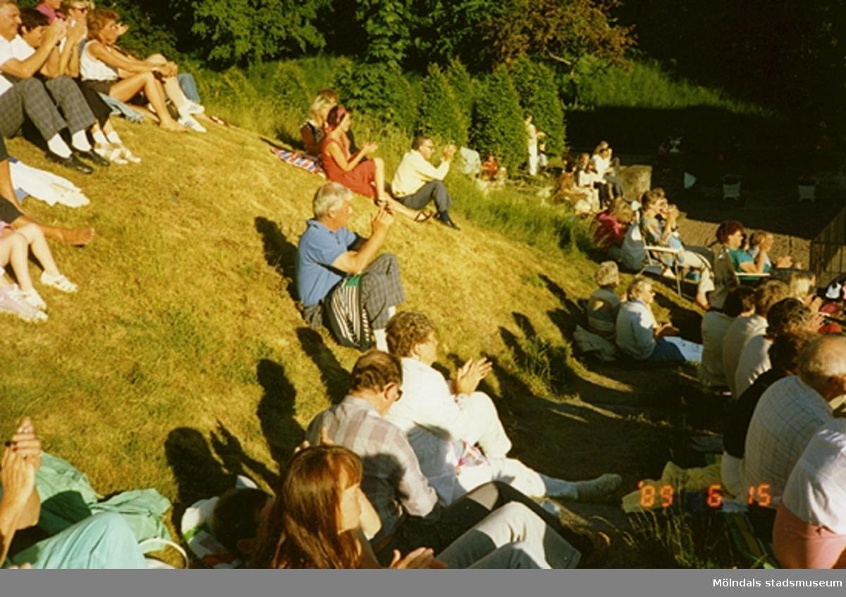 Folk sitter och solar sig och klappar takten till musiken som spelas.