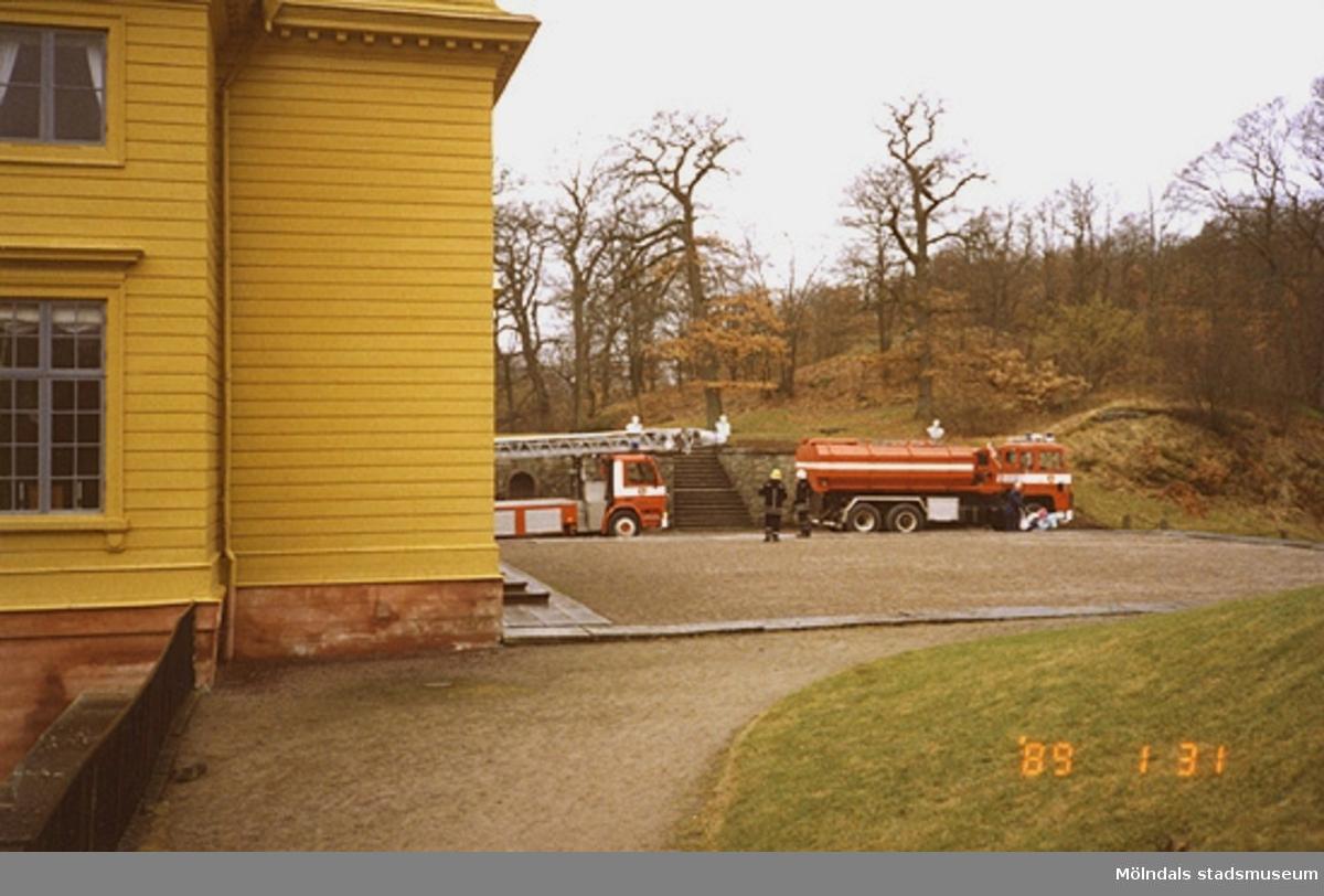 Två brandbilar och brandmän står uppställda framför slottet, nedanför kejsarterrassen.