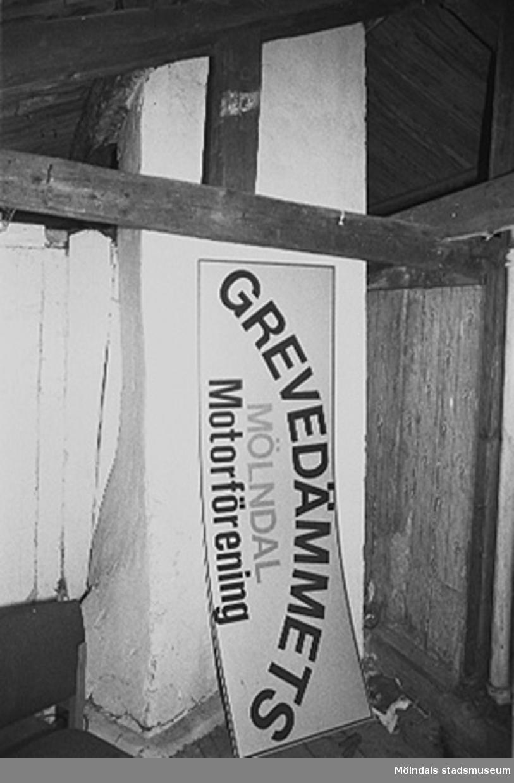 """Skylt lutad mot en pelare: """"GREVEDÄMMETS MÖLNDAL Motorförening"""" i Röda huset, G-3. Interiör av vinden. Den murstock som i mitten av huset går genom de tre våningarna. Mycket gamla tapeter syns på väggen till höger om murstocken. Tapetprover lämnades till Mölndals museum 1995, för analys."""