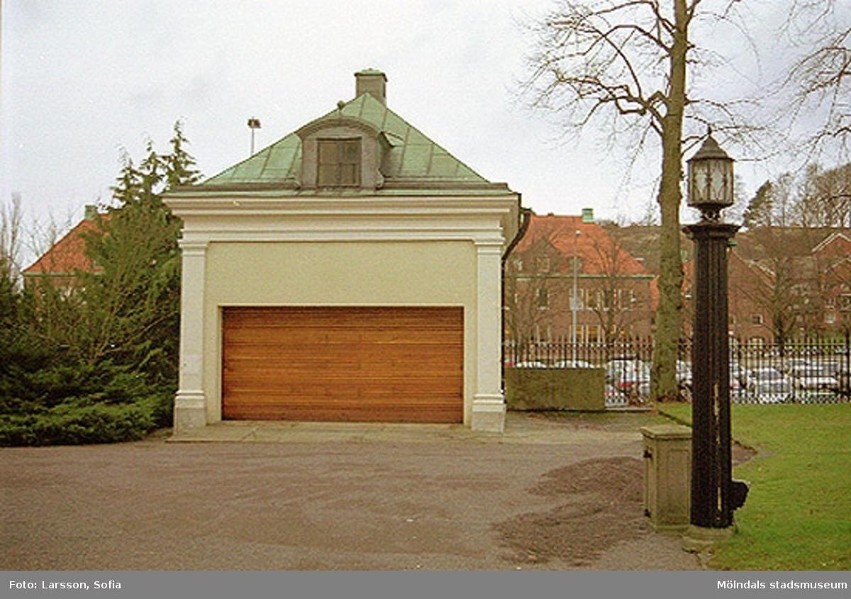 Garagebyggnad tillhörande Villa Papyrus. I bakgrunden syns parkerade bilar samt den röda tegelbyggnaden Kvarnbyskolan.