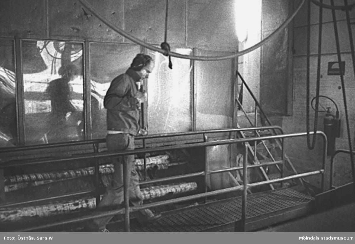 En man i arbete med träråvara.Bilden ingår i serie från produktion och interiör på pappersindustrin Papyrus.