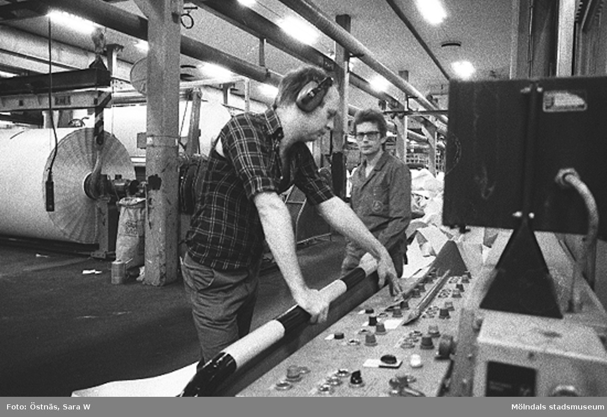 Två män i arbete. Byggnad 6, manöverbordet till KM 2. Denny Andersson och Anders Severed. Bilden ingår i serie från produktion och interiör på pappersindustrin Papyrus.