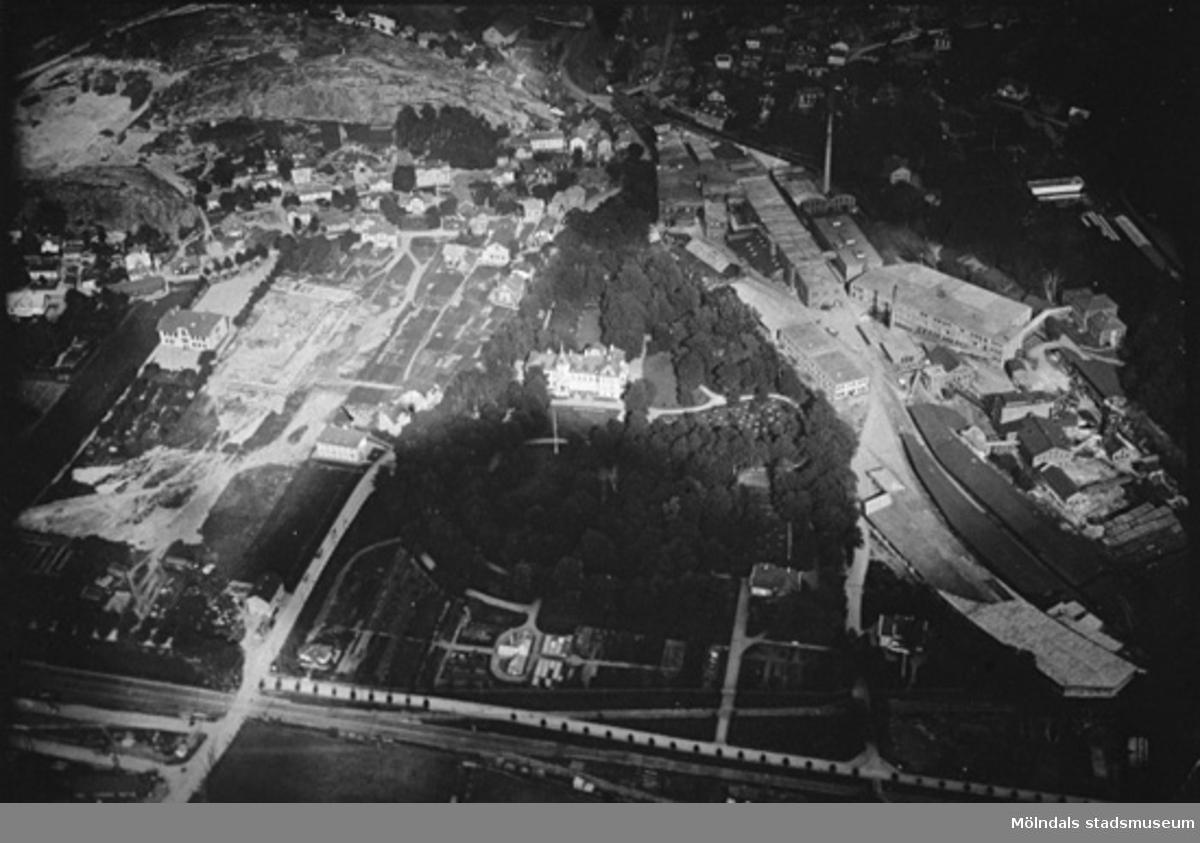Flygfoto från väster över stadsdelen Trädgården och Papyrus. Kvarnbyskolan håller på att byggas 1923 eller 1924. Mitt i bild ser vi Papyrus kontor inbäddat i grönska och i husgruppen till vänster därom, ser vi Apoteket och ett hus där det under en tid fanns en tvättinrättning av något slag. Sist syns huset där restaurang Godhem inrymdes. På Papyrusområdet syns en byggnad i lite diagonalt läge som kallades för Kromo. Vägkorset i vänster underkant är blivande Mölndalsbro.
