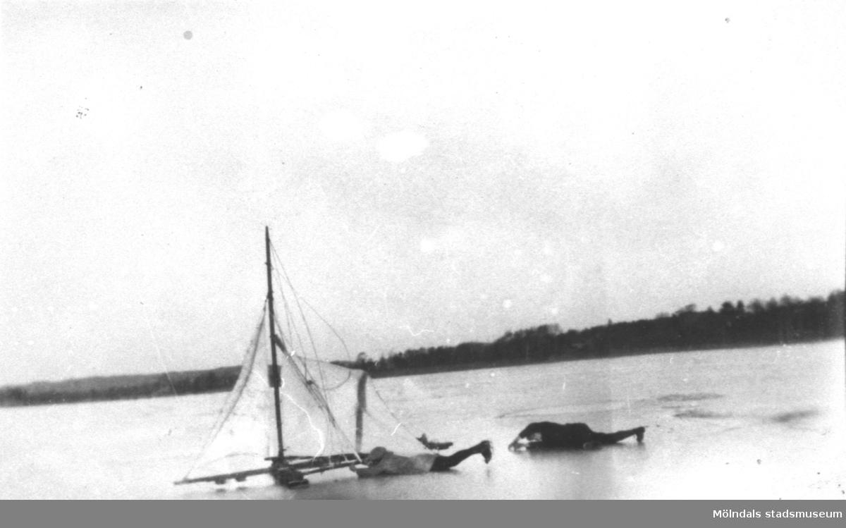 Två personer åker skridskor efter segel på istäckt Tulebosjön. En av de två är Östen Krantz, bror till Rosa Pettersson, född Krantz.