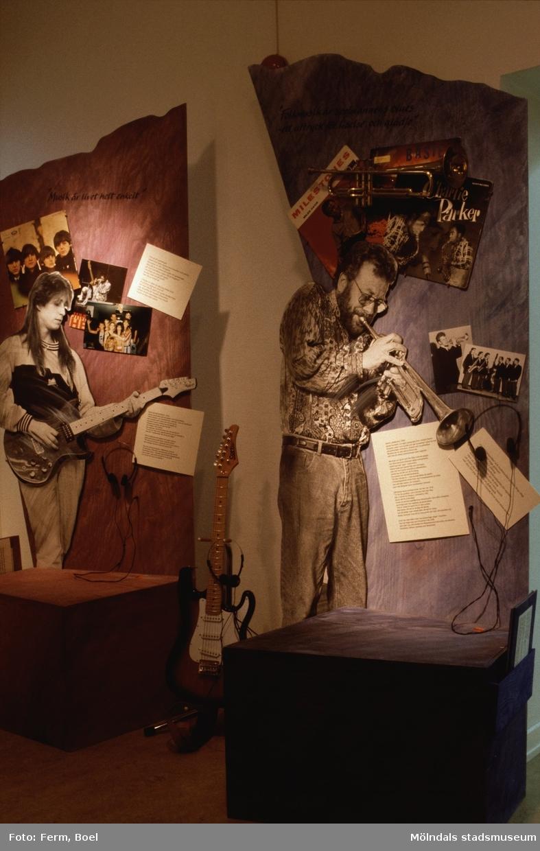 """Fotografi som visar utställningen """"Från näckens polska till rockens roll"""" på Mölndals museum.  Utställningen """"Från näckens polska till rockens roll"""" på Mölndals Museum, Norra Forsåkersgatan 19, Mölndal, pågick från 1 december 1990 till 31 december 1991. En utställning om folkmusik och folklig musik. Är rockmusik dagens folkmusik och vad har discodansen gemensamt med dansen i vägskälet? Vad har musik och dans för funktion egentligen?"""
