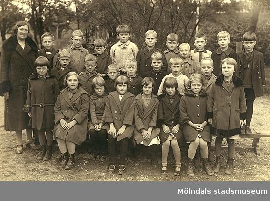 """Skolfröken fröken Lundgren med skolklass från Grevedämmets skola, år 1926.Barnen står vända mot skolan, bakgrunden vetter mot """"Kråkan"""" och Kvarnbyn.På bilden är 4:e person från vänster givaren själv Gustaf Henriksson, 1:e från vänster Leif Olssén, i mellan Erik """"Lill-Erik"""" Karlsson, överst i mitten Bengt Ruustad (Johansson) och i mitten Bengt Sylvén (fick senare en karriär inom militären i finsk, ryska kriget).Givaren Gustaf bodde vid skolgården i Lackarebäck, Roten D 22A, nuv. Utmarksgatan 13. Han är född 1919."""
