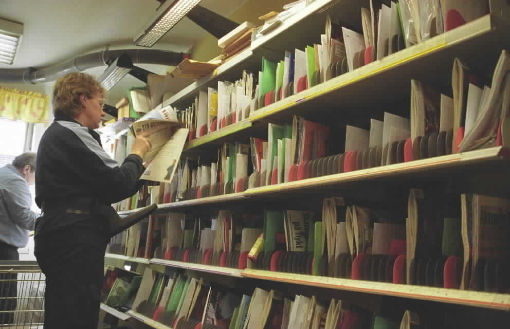 Brevbärare Lisbeth Friberg, posten i Knivsta, sorterar post. På magen har hon en hållare för posten.