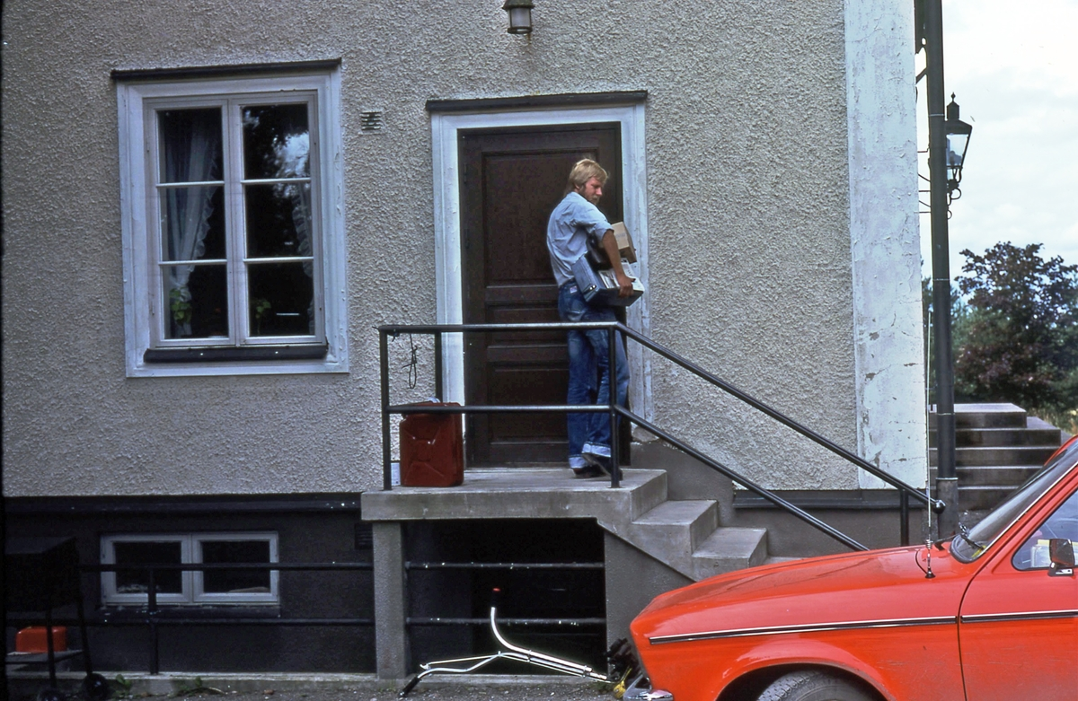 Lantbrevbäraren Mikael  Mattsson vid Hacksta Gård. Han står uppe på trappan, utanför dörren med post under armen. I förgrunden ser man den röda bilen.