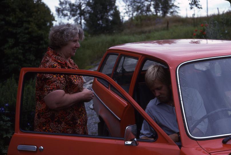 Lantbrevbäraren Mikael Mattsson besöker Maj-Britt Wessberg i Räfsta i Vallentuna. Han sitter i bilen, hon står vid den öppna bildörren.