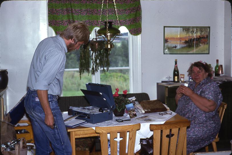 Lantbrevbäraren Mikael Mattsson och Karin Jansson hemma hos henne i i Räfsta. Han hjälper henne med postärenden. Kassaskrinet är öppet.