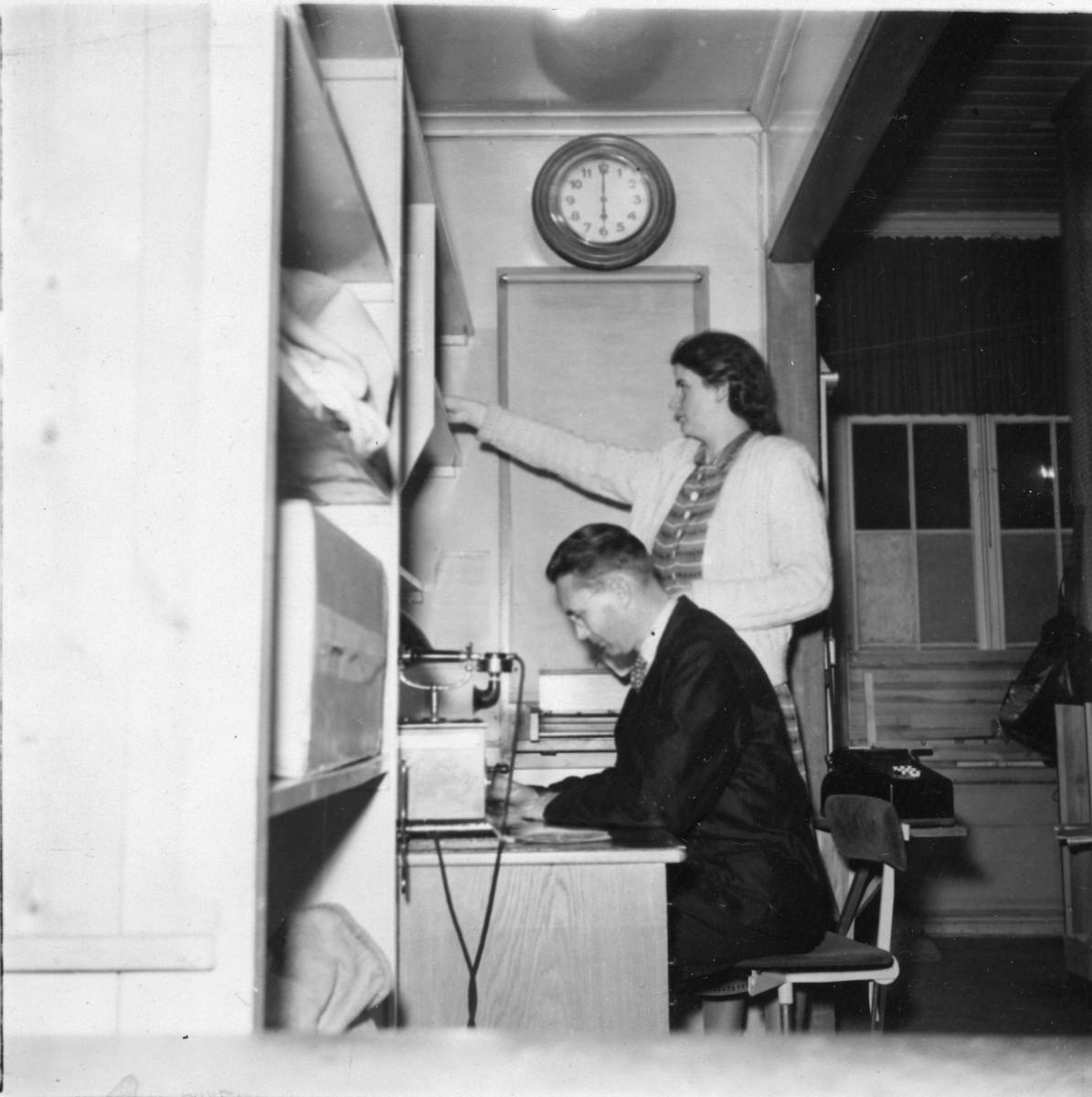 Poststationen i Habo, Västergötland. Sista dagen i den gamla lokalen den 3 november 1949. Stationsmästare Bergmer och postbiträdet Mary Fogelström.