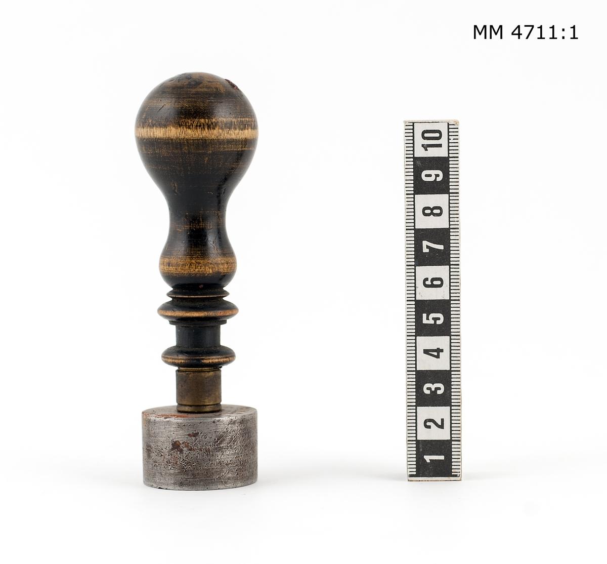 Sigill av stål. Cylindriskt med svarvat handtag av svartpolerat trä. Text: H.M. Pansarbåt Svea, dessutom ankare med kunglig krona omgivet av tre mindre kronor.